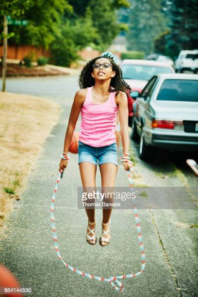 Teenage girl jumping rope on neighborhood sidewalk