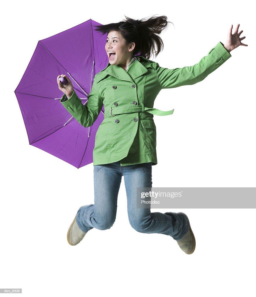 Teenage girl jumping with an umbrella : Foto de stock