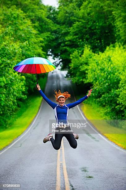 Teenage girl jumping with umbrella on road, Bainbridge Island, Washington, USA