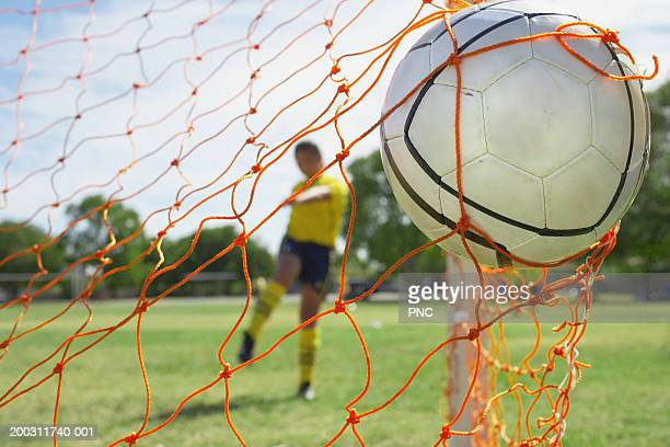 Teenage girl (16-18) kicking soccer ball into goal (focus on ball)