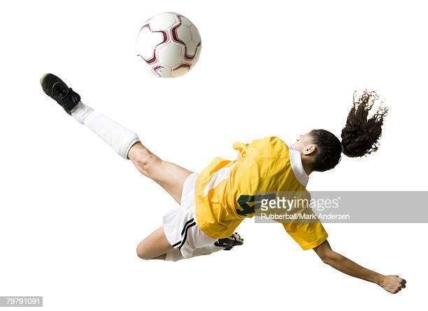 Teenage girl kicking soccer ball