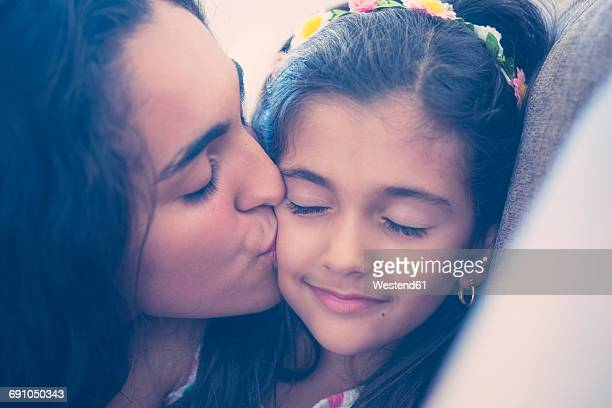 Teenage girl kissing her little sister