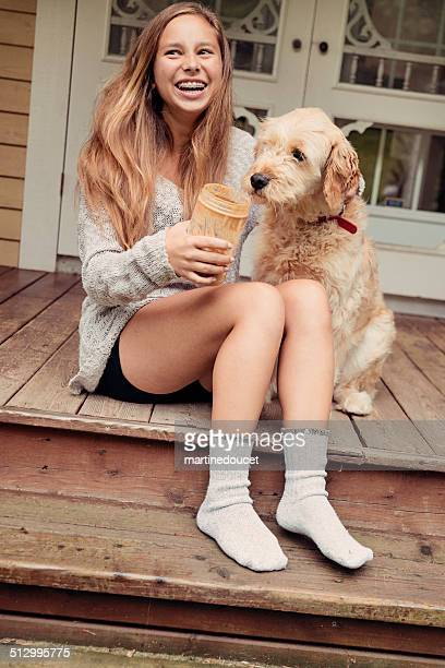 teenage girl laughing with dog and peanut butter on porch. - goldendoodle stock photos and pictures