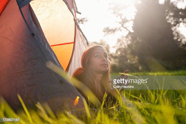 Teenage girl laying in tent at campsite
