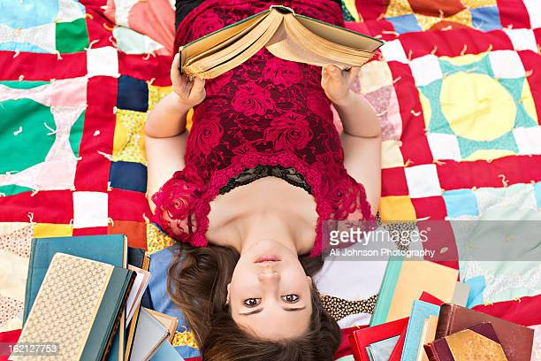 Teenage girl lays on a blanket reading