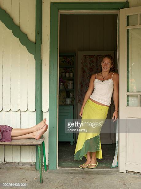 Teenage girl (14 -16) leaning against door frame, smiling, portrait