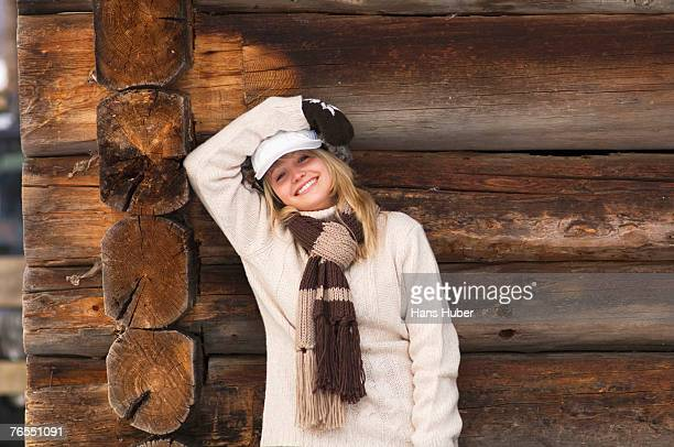 Teenage girl (16-17) leaning on wooden wall, smiling, portrait