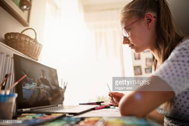 teenage girl learning painting from youtube - tutorial stock pictures, royalty-free photos & images