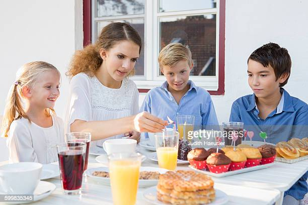 Teenage girl lighting birthday cake candles for children at patio table