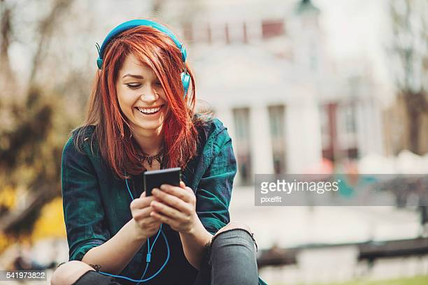 teenage girl listening music from a smart phone - dyed red hair stock pictures, royalty-free photos & images