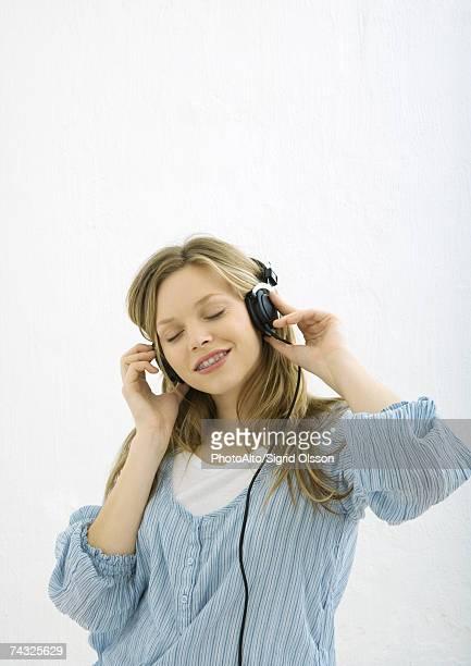 Teenage girl listening to headphones, portrait