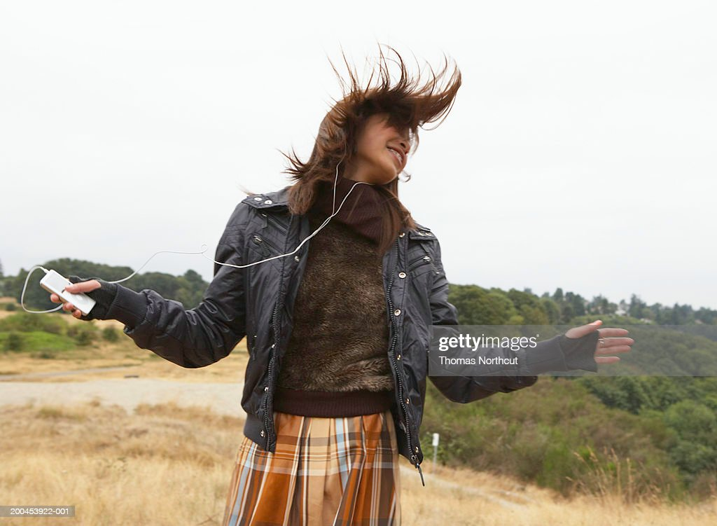 Teenage girl (15-17) listening to MP3 player, dancing (blurred motion) : Stock Photo