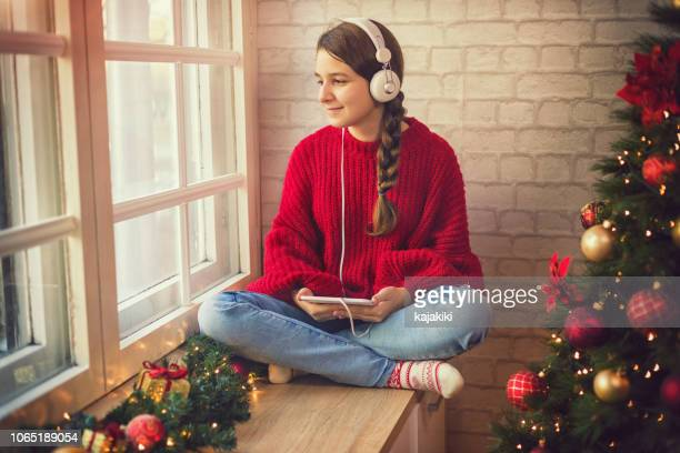 teenage girl listening to music in cozy christmas atmosphere - christmas music stock pictures, royalty-free photos & images