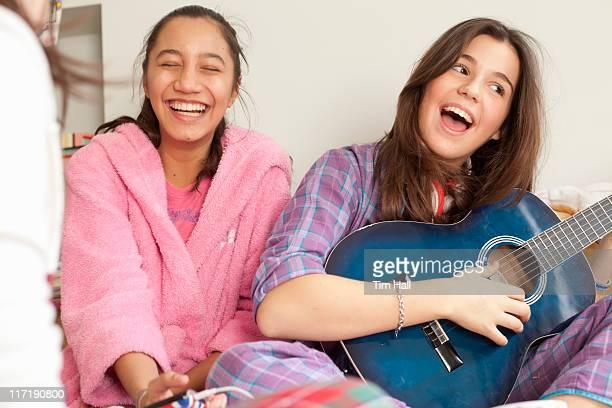 Adolescente ragazza ascoltando musica in pigiama