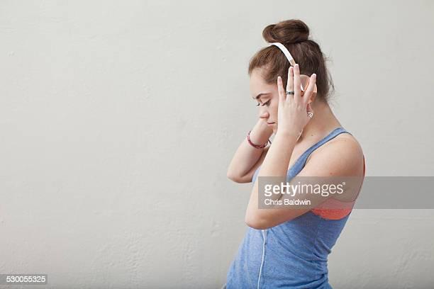 Teenage girl listening to music on headphones in ballet school