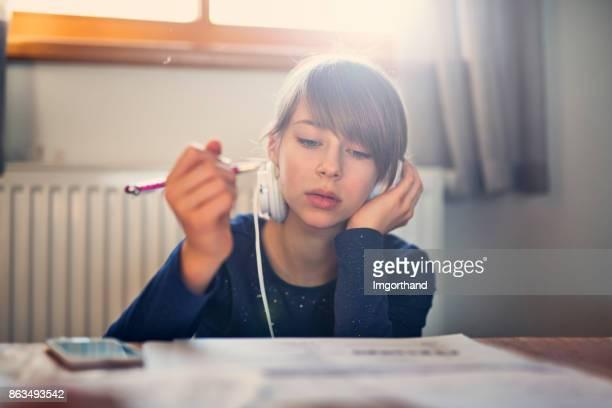 Teenage girl listening to music while doing homework