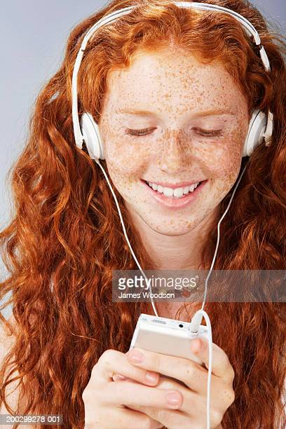 Teenage girl (13-15) listening to personal stereo, smiling, close-up