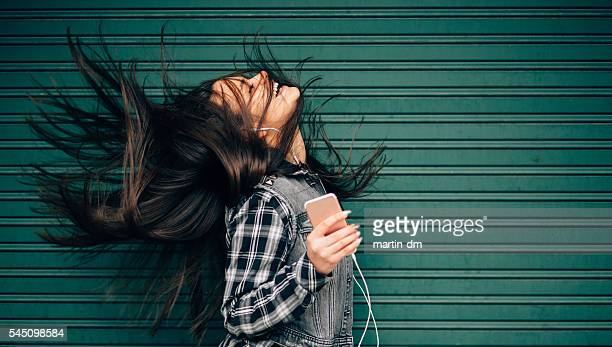 teenage girl listening to the music and shaking head - muziek stockfoto's en -beelden