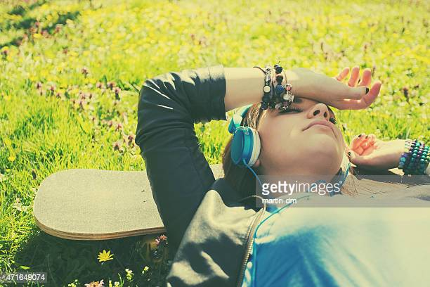 Teenage girl listening to the music in the grass