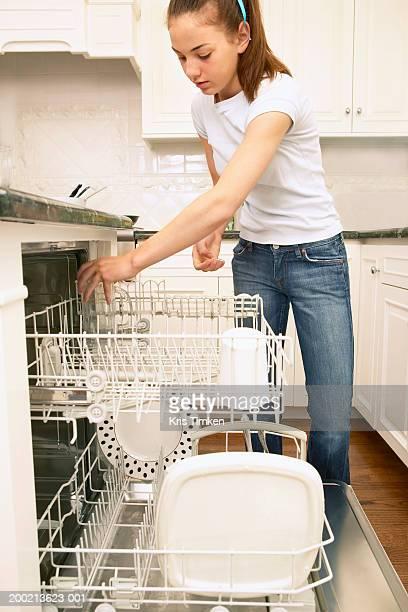 Teenage girl (12-14) loading dishwasher in domestic kitchen