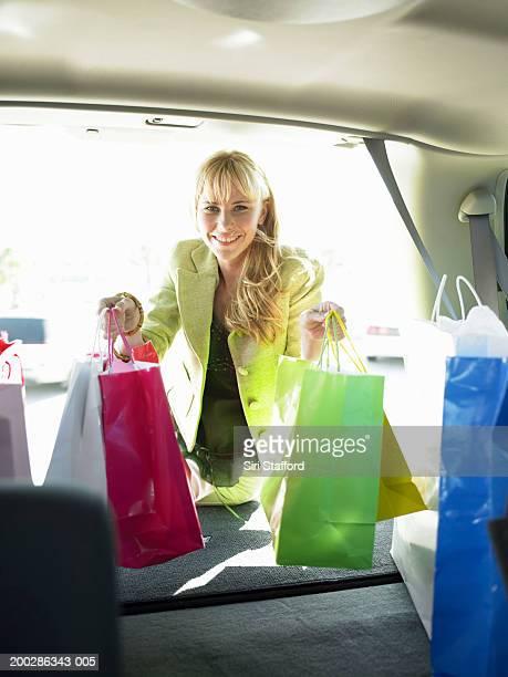Teenage girl (17-19) loading shopping bags in back of car