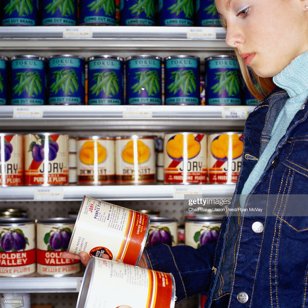 Teenage girl (14-16) looking at cans in supermarket, side view : Stock Photo
