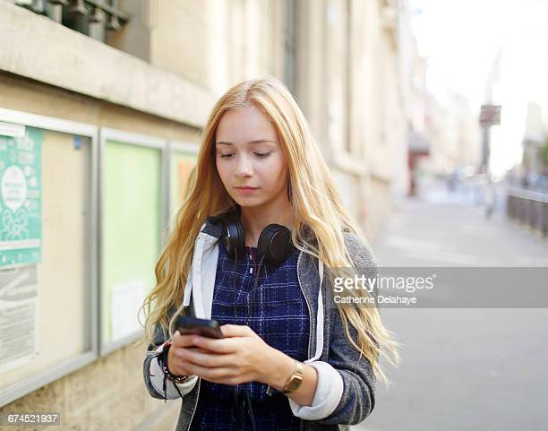 a teenage girl looking at her cell phone - hoodie headphones stock pictures, royalty-free photos & images