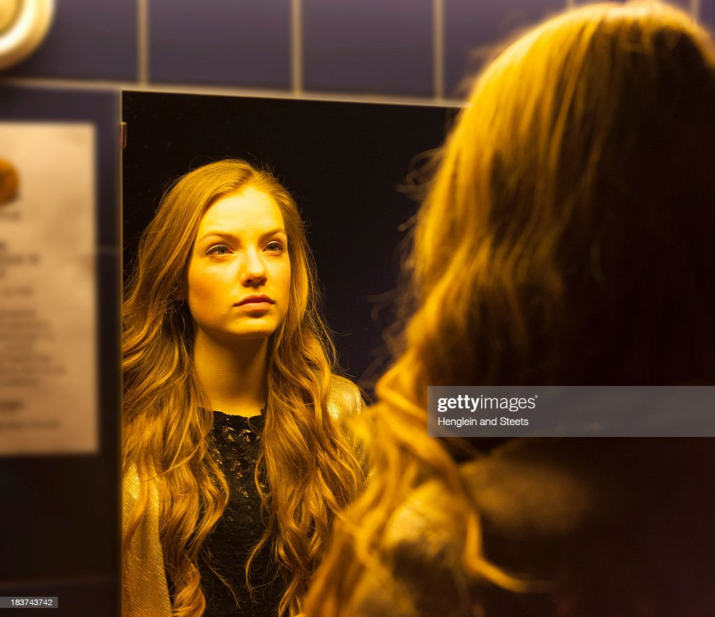 Teenage girl looking at her reflection in mirror : Stock Photo