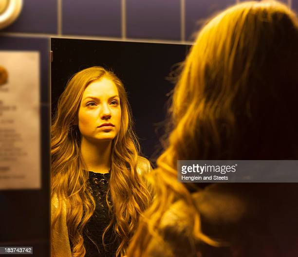 teenage girl looking at her reflection in mirror - girl in mirror stock-fotos und bilder