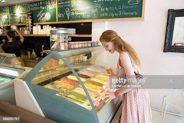 Teenage girl looking at ice cream in an ice cream.