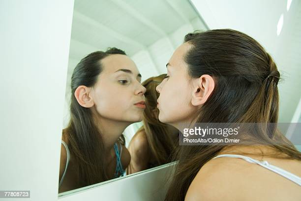 Teenage girl looking at self in mirror, kissing her reflection