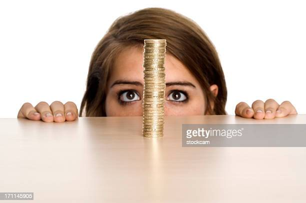 Teenage girl looking at stack of Pound coins