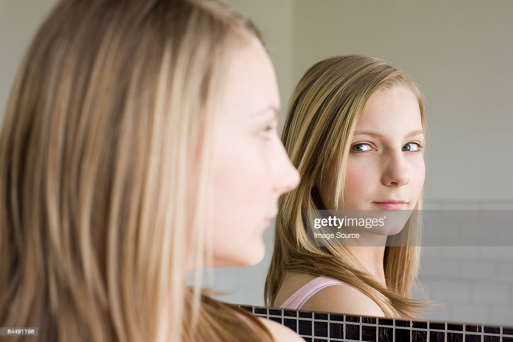A teenage girl looking in a mirror : Stock Photo