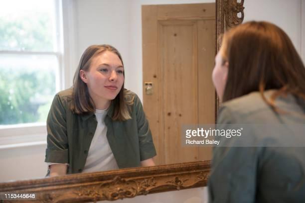 teenage girl looking in bathroom mirror - ひげそり用鏡 ストックフォトと画像