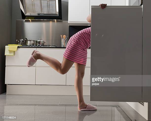 teenage girl looking into refrigerator for midnight snack