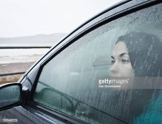 Teenage girl looking out wet car window