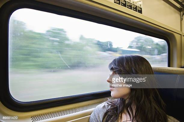 Teenage girl looking out widow of train