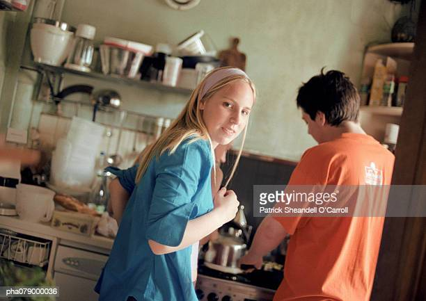 Teenage girl looking over shoulder at camera, in kitchen, next to teenage boy, rear view, tilt.