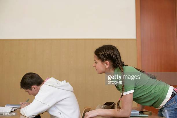 Teenage girl looking over teenage boy's shoulder