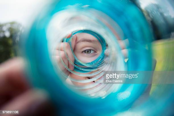 teenage girl looking through a blue coiled slinky toy - looking through an object stock pictures, royalty-free photos & images