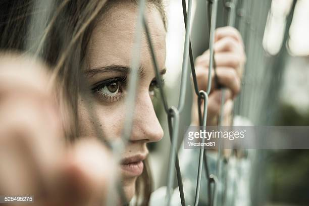 teenage girl looking through a wire fence - wire mesh fence stock pictures, royalty-free photos & images