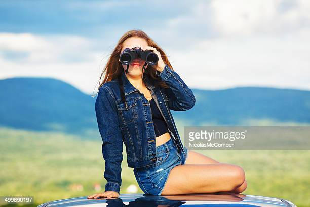 Teenage girl looking through binoculars
