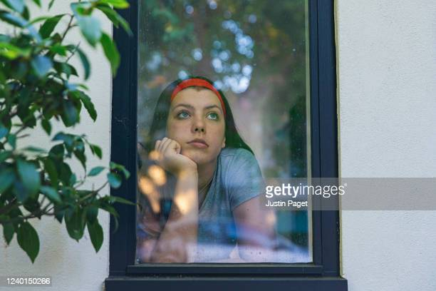 teenage girl looking through window - boredom stock pictures, royalty-free photos & images