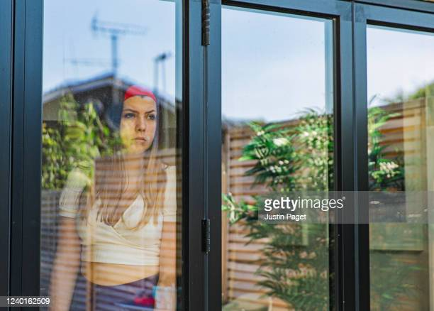 teenage girl looking through window - depression sadness stock pictures, royalty-free photos & images