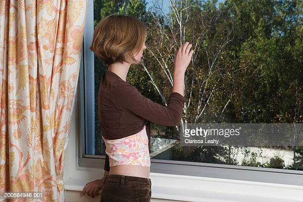 teenage girl (16-17 years) looking through window, side view - 16 17 years stock pictures, royalty-free photos & images