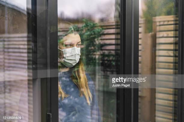 teenage girl looking through window with mask - quarantäne stock-fotos und bilder