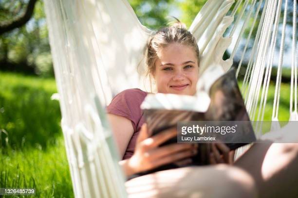 teenage girl looking up from her book in a hanging seat in her orchard - lucy lambriex stockfoto's en -beelden