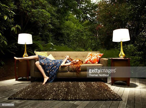 Teenage girl lounging on sofa outdoors