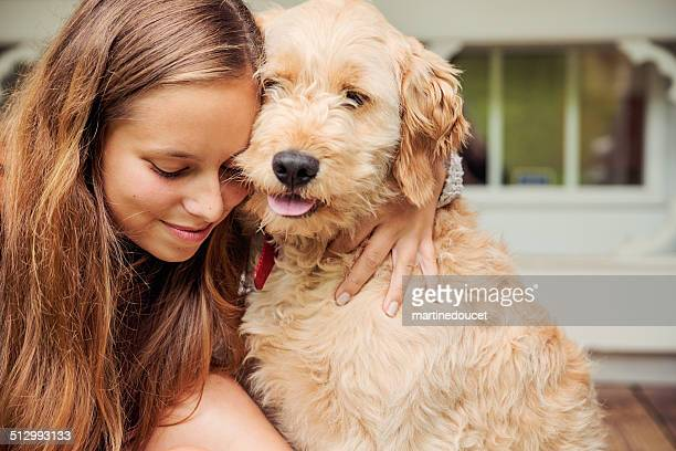 teenage girl lovingly hugging her goldendoodle dog on porch. - goldendoodle stock photos and pictures
