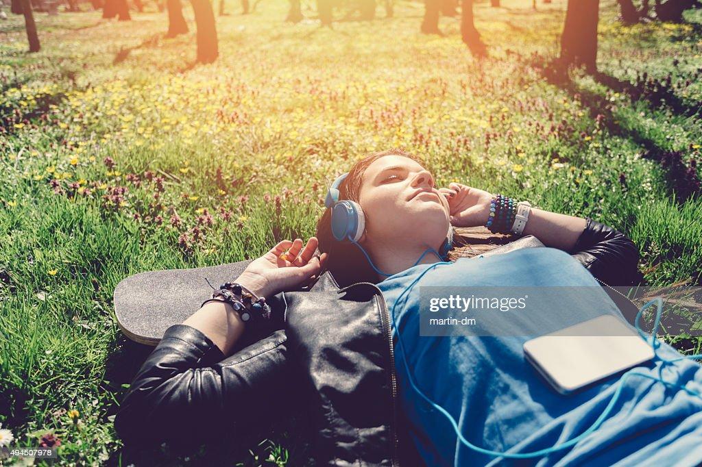 Teenage girl lying down in the grass : Stock Photo
